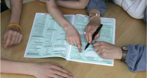 A family fills out a census form in 2011.  Photograph: Dara Mac Dónaill
