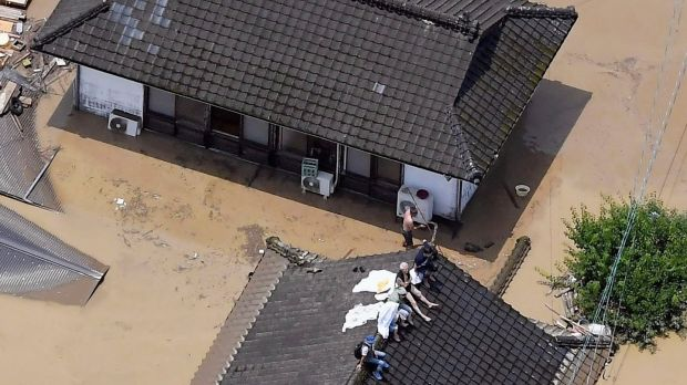 Residents are stranded on the rooftop of a house submerged in muddy waters that gushed out from the Kuma River in Hitoyoshi, Kumamoto prefecture, southwestern Japan. Photograph: Kyodo News via AP