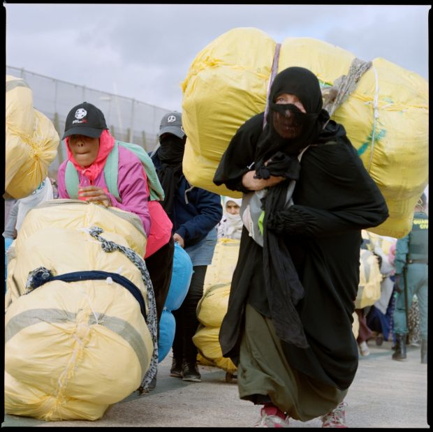 A Moroccan woman carries a package on her back at the Barrio Chino border crossing.