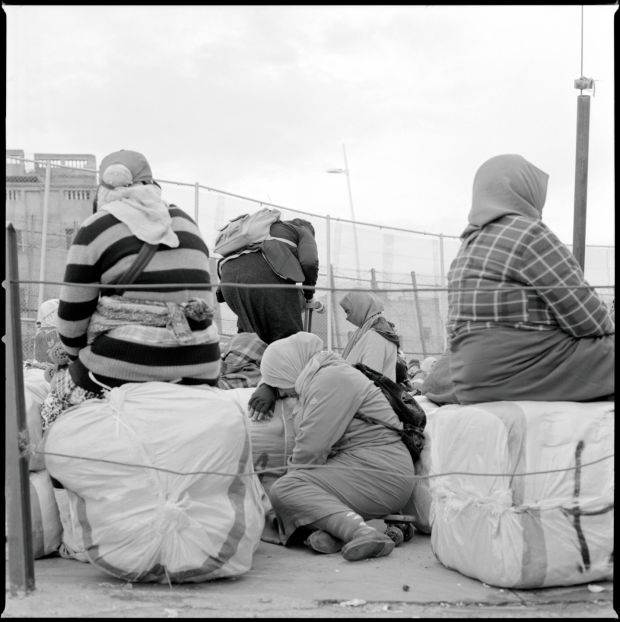 Morcoccan women wait with their packages at the Barrio Chino border crossing point in Melilla.
