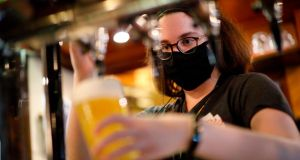 Covid precautions: a masked bartender pours a pint in a London pub. There is mounting evidence coronavirus is airborne, making enclosed indoor spaces more dangerous. Photograph: Tolga Akmen/AFP/Getty