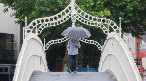 KEEP THE HEAD DOWN: People braving the bad weather on the Ha'penny Bridge in Dublin. Photograph: Gareth Chaney/Collins