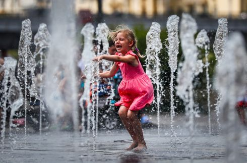 COOLING OFF: A girl beats the heat by standing in a fountain in Moscow as temperatures exceed 30 degrees in the Russian capital. Photograph: Yuri Kochetkov/EPA