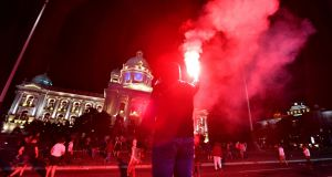 Protester holds flare as Serbian police fires tear gas in front of the National Assembly building in Belgrade. Photograph: Andrej Isakovic/AFP