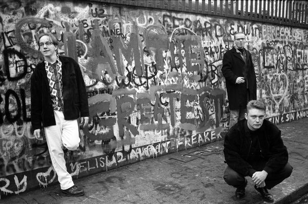 "A House, in Dublin, in Devember 1991. Dave Couse left, in front of graffiti painting the name of their album ""I Am The Greatest"" ouside U2's studios. (Photo by Martyn Goodacre/Getty Images)"