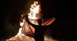 A loyalist waves the  union flag at the Ballycraigy estate 11th night bonfire in Antrim, Northern Ireland. Photograph: Getty