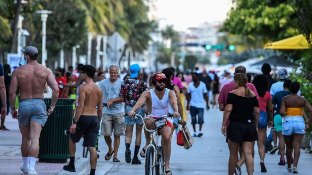 People cycling and walking along Ocean Drive in Miami Beach, Florida in late June. Photograph: Chandan Khanna/AFP/Getty