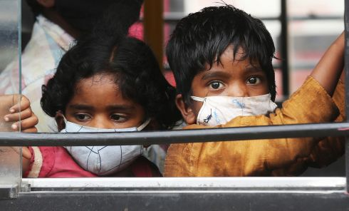TRAVEL COVER: Indian children wear masks as they travel by bus, in Bangalore, India. Photograph: Jagadeesh NV/EPA