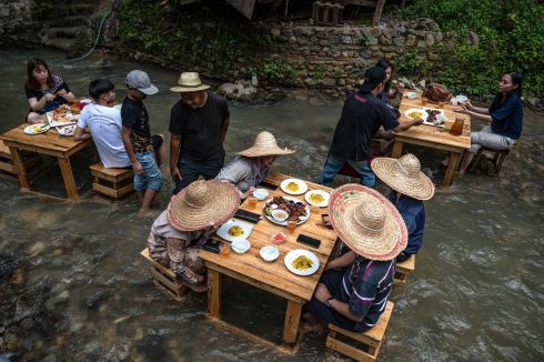 OUT TO LUNCH: Customers eat lunch at a restaurant with tables in a stream of a river, in Kampung Kemensah on the outskirts of Kuala Lumpur, Malaysia. Photograph: Mohd Rasfan/AFP via Getty Images