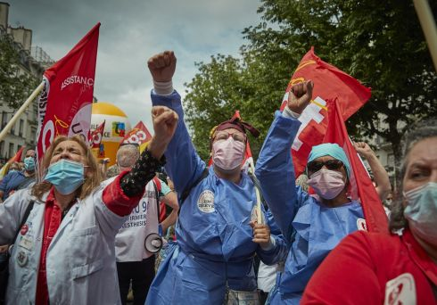 BASTILLE DAY RALLY: Health workers and union members chant during an anti-government protest on Bastille Day near Place de la République in Paris, France. Photograph: Kiran Ridley/Getty Images