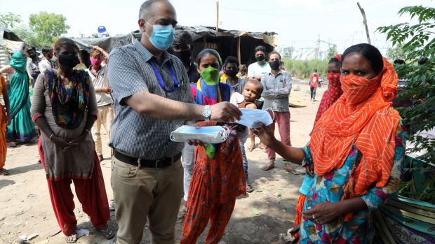 A medical officer distributes masks to the residents in Jammu, India. Photograph: Jaipal Singh/ EPA