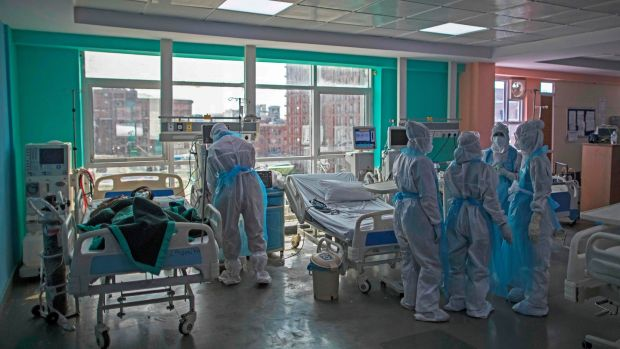 Doctors and nurses wearing Personal Protective Equipment (PPE) gather next to a coronavirus patient at the intensive care unit of the Sharda Hospital in Greater Noida. Photograph: Xavier Galiana/AFP/Getty