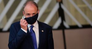 Taoiseach Micheál Martin takes off a protective face mask as he arrives in Brussels on Friday as EU leaders hold their first face-to-face summit over a post-virus economic rescue plan. Photograph: Francisco Seco/AFP