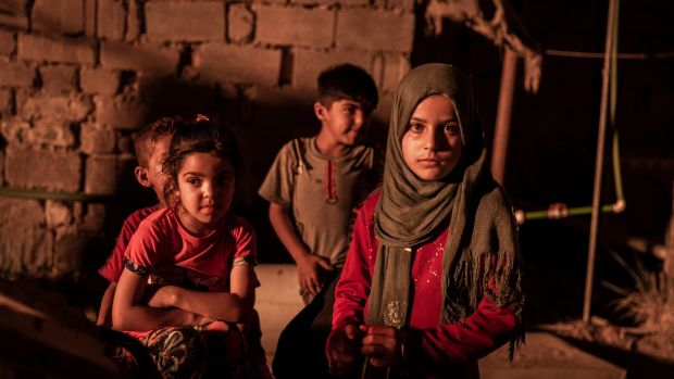 Children in a compound courtyard near flaring oil wells that light the night sky in Nahran Omar in Iraq. Photograph: Ivor Prickett/New York Times