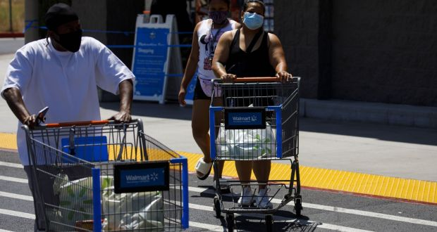 Shoppers wearing protective masks leave a Walmart store in Lakewood, California. Photograph: Bloomberg