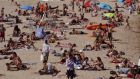 Beachgoers bask in the sun at La Nova Icaria beach in Barcelona, Spain, on Friday. Photograph:   EPA