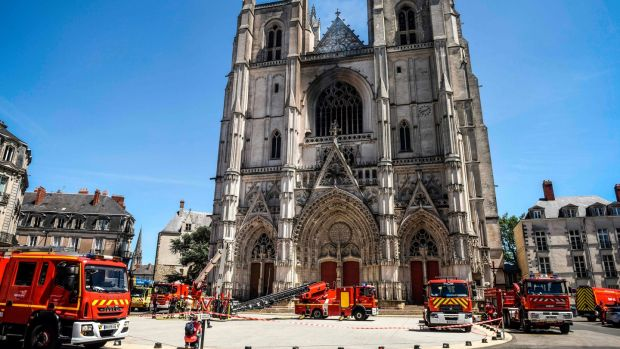 Firefighters at work at the Cathedral of St Peter and St Paul in Nantes on Sunday after a fire ravaged parts of the Gothic building before being brought under control. Photograph: Salom-Gomis/AFP