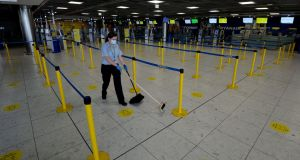 A member of the cleaning staff  at Dublin Airport. The use of face masks is a remarkably efficient way of reducing contagion. Photograph: Alan Betson.