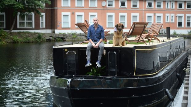 Gary Long with his dog, Kimba, on his barge moored on the Grand Canal in Dublin. Photograph: Dara Mac Dónaill