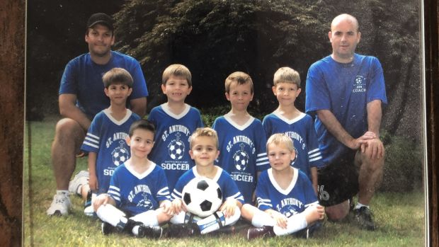 "A wooden plaque with a photograph of an under-8 soccer team in 2007, Abe Hannigan a towheaded imp grinning in the middle row (3rd right), me a dome-headed character at the back in a shirt that helpfully said ""coach""."