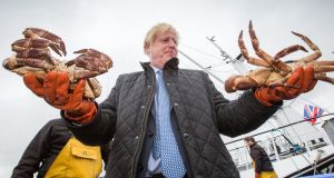 British prime minister Boris Johnson holding  crabs  at Stromness harbour during a visit to the Scottish Highlands and Northern Isles. Photograph:   Robert Perry/PA Wire