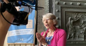 Anne Soupa being interviewed on the porch of the Église de la Madeleine. Photograph: Lara Marlowe