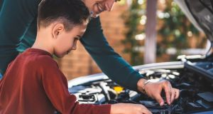 Show your kids the basics of car maintenance such as putting water into the engine and filling up the windscreen wiper. Photograph: iStock