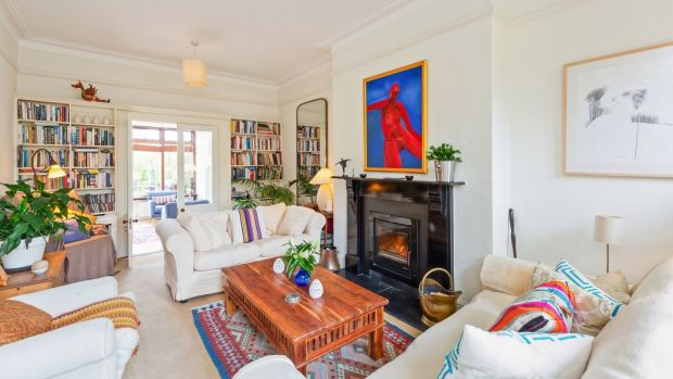 Cosy sitting room, with squishy, linen-covered seating set around a black painted fire surround, with an inset Heat Design stove