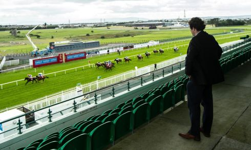 A STRANGE DAY: Trainer Ado McGuinness watches the second race, the Claytonhotelgalway.ie Handicap, from an empty stand on the first day of the Galway Racing Festival. Photograph: James Crombie/Inpho