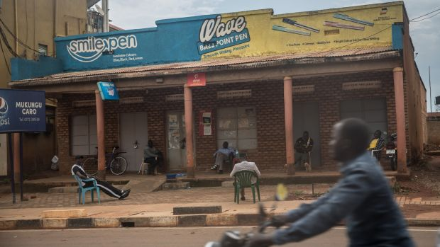 Ugandans sit in spaced-out plastic chairs outside Mukungu Caro bar. Photograph: Sally Hayden