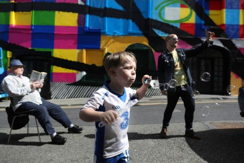 Conor Tyler (4) from Waterford blowing bubbles with festival volunteers Piotr Seweryn and Ivan Jelacic pictured at the launch of Waterford Walls Street Art Festival. The timing of this year's festival has been extended to ensure it complies with COVID-19 safety measures and it runs from the 12th of July to the end of August with 13 artists involved. Photograph : Julien Behal