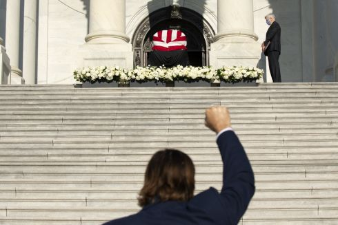 A visitor raises a fist in the air near the American flag-draped casket of the late Representative John Lewis on the steps of the U.S. Capitol in Washington, D.C., U.S., on Tuesday, July 28, 2020. Lewis, a civil rights leader who was one of the original Freedom Riders and became a leading liberal voice for decades in the U.S. House of Representatives, died on July 17 at the age of 80. Photographer: Stefani Reynolds/Bloomberg