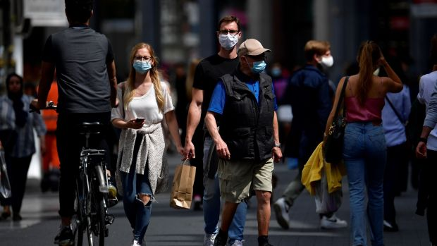 People wear protective face masks as they walk in the centre of Antwerp. To combat an outbreak of Covid-19 the city has imposed a curfew from 11.30pm to 6am. Photograph: John Thys/AFP via Getty Images