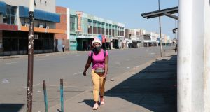 A woman walks on a deserted street in the central Harare, Zimbabwe, where there is a  6pm-6am curfew. Photograph: EPA/Aaron Ufumeli