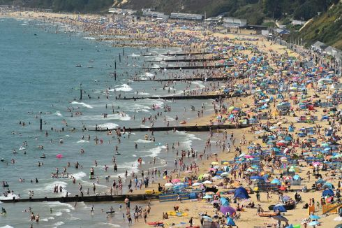 BY THE SEA: Beachgoers enjoy the sunshine as they sunbathe and play in the sea on Bournemouth beach in Bournemouth, England on Fridayas temperatures soar across the country. Photograph: Glyn Kirk/AFP/Getty