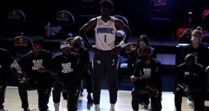 Jonathan Isaac stands as his team mates kneel before the start of a game between the Brooklyn Nets and the Orlando Magic. Photograph: Getty Images