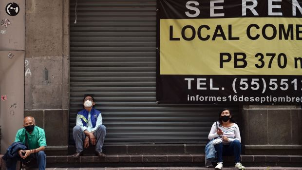 People wear face masks outside a closed shop for rent in Mexico City. Photograph: Rodrigo Arangua/Getty/AFP