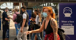 Commuters wearing protective face masks in Manchester Piccadilly railway station. Photograph: Ian Hodgson/Bloomberg