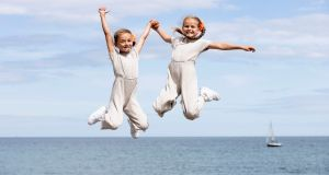 THAT HOLIDAY FEELING: Sophia (7) and Layla Rose Deegan (8), from Ballymun, jump for joy at Bray seafront in Bray, Co Wicklow. Photograph: Tom Honan