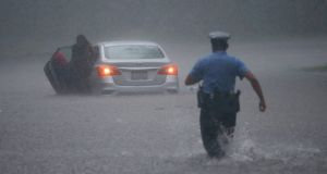 A Philadelphia police officer rushes to help a stranded motorist during tropical storm Isaias, Tuesday, August 4th, 2020, in Philadelphia. Photograph: Matt Slocum/AP
