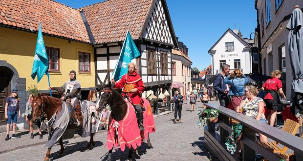Two members of a knight society  carry flags reading 'Keep distance' and 'Wash your hands often' through the city of Visby on popular Swedish holiday destination,  Gotland island.  Photograph: EPA