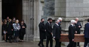 Patricia Hume (centre in grey jacket) walks behind her husband's casket as it is carried from St Eugene's Cathedral in Derry, following his funeral service on Wednesday. Photograph: Niall Carson/PA Wire