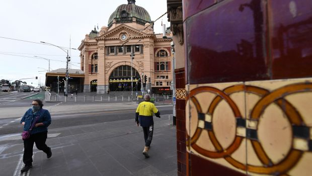 A person wearing a face mask walks outside of Flinders Street Station in Melbourne, Australia, August 6th 2020. Photograph: James Ross/EPA