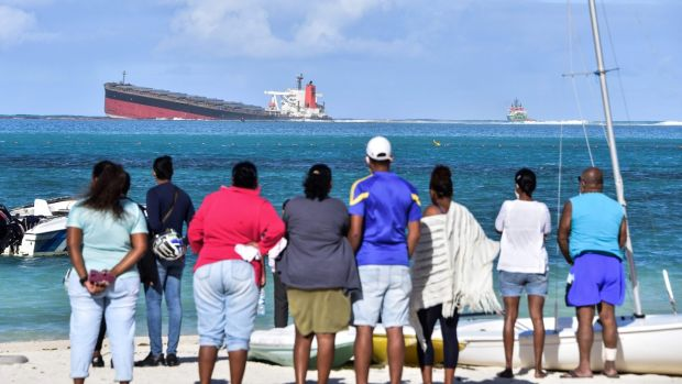 People look at MV Wakashio bulk carrier that ran aground off southeast Mauritius. Photograph: Dev Ramkhelawon/L'Express Maurice/AFP/Getty Images