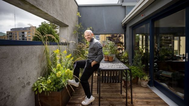 Mark Grehan in his garden. The terrace's outer concrete boundary walls are painted a warm shade of charcoal-grey that mirrors the interior walls of his apartment. Photograph: Tom Honan