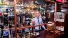 John O'Brien, manager of Doheny & Nesbitt, serving pints behind a perspex screen. Photograph: Gareth Chaney/Collins