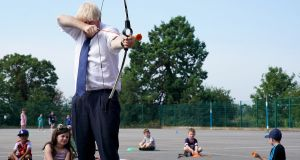 COVID CRACKDOWN: British prime minister Boris Johnson takes aim with a bow and arrow at St Joseph's Catholic Primary School, Upminster, London, as he surveys Covid-19 preparations ahead of school pupils in England returning to class in September. Photograph: Pippa Fowles/Handout/EPA