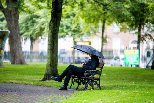 SUMMER IN DUBLIN: A man waits out a rain shower under an umbrella in the park at Mountjoy Square, Dublin city. Photograph: Tom Honan