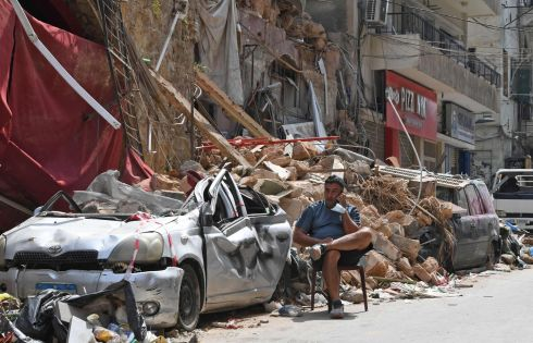 BEIRUT PORT EXPLOSIONS: A Lebanese man talks on the phone while seated by the rubble of a destroyed building in Beirut's Gemmayzeh neighbourhood. Photograph: AFP via Getty Images