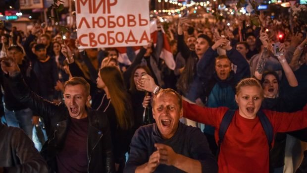 "People shout as they hold a poster reading ""Peace, Love, Freedom"" in Minsk on Thursday. Photograph: Sergei Gapon/AFP via Getty Images"
